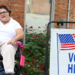 """A woman in a wheelchair next to a sign that says """"Vote here"""""""