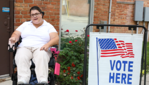 "A woman in a wheelchair next to a sign that says ""Vote here"""