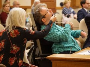 Ramsey Lee testifies in hearing room while a woman holds his microphone.