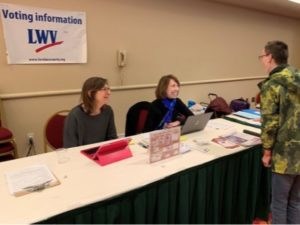 "Two women sitting at outreach table labeled ""Voting Information - LWV"", helping a visitor"