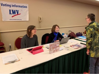 """Two women sitting at outreach table labeled """"Voting Information - LWV"""", helping a visitor"""