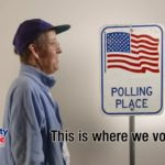 "Man in baseball cap standing next to sign with an American flag on it that says ""Polling Place"""
