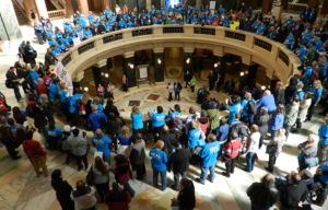 People in blue t-shirts standing around the rotunda at the Wisconsin Capitol on Disability Advocacy Day