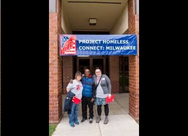 Three people standing in front of building with a Project Homeless Connect banner hanging in the doorway