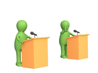 Two figures standing at podiums