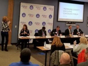 County executive forum candidates sitting at table in front of audience