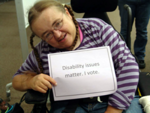 "Woman sitting in chair holding sign that says ""Disability issues matter. I Vote."""