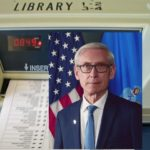 Ballot machine with portrait of Governor Evers superimposed over it
