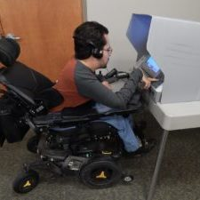 Bill Crowley in his wheelchair using an accessible voting machine